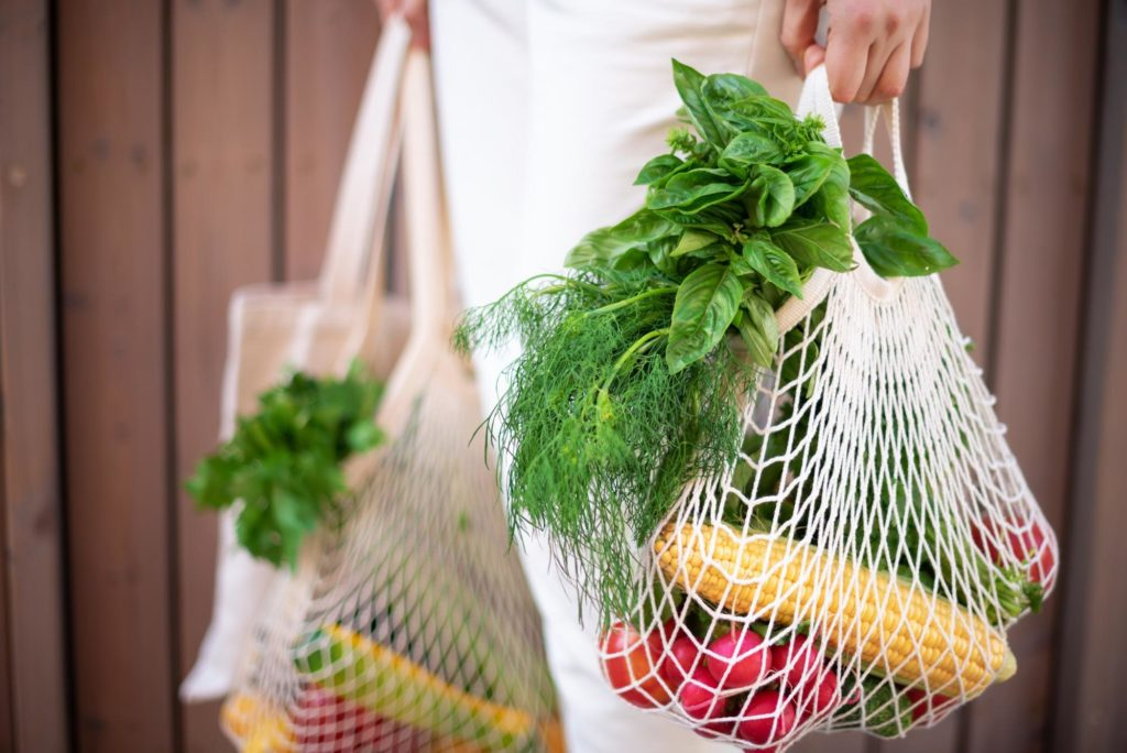 organic fruits and veggies in an eco friendly reusable bag